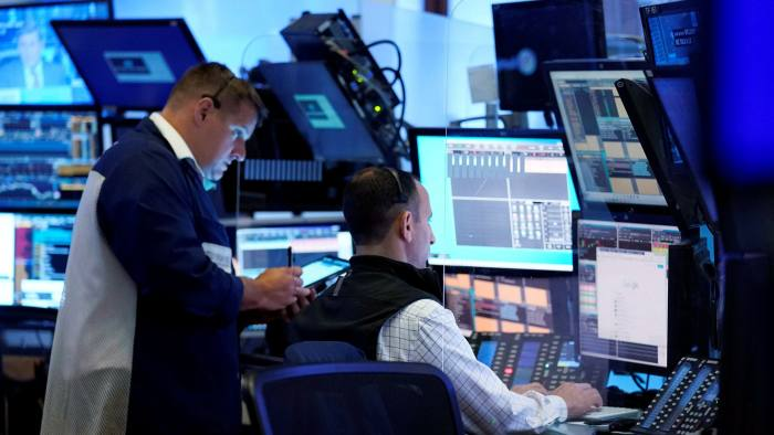 A pair of traders work on the floor of the New York Stock Exchange