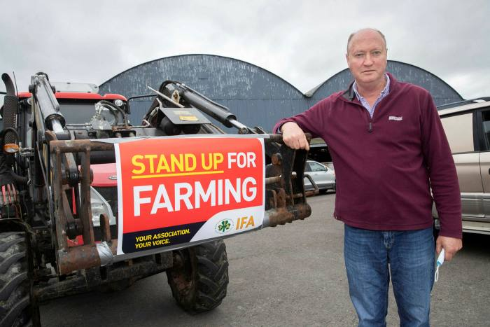 A man leaning against a digger bearing a Stand Up For Farming sign