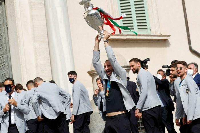 Giorgio Cielini detiene il trofeo del Campionato Europeo mentre il presidente Sergio Matterella dà il benvenuto alla squadra italiana lunedì al Guerrero Palace di Roma
