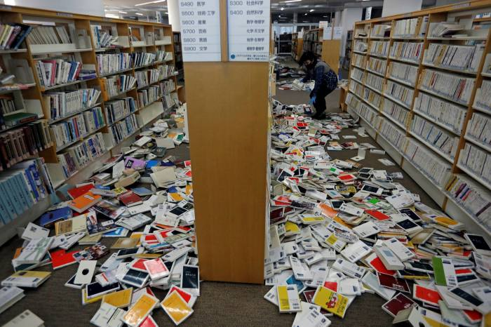 A library staff member restores books after they fell from book shelves during an earthquake in Iwaki, Fukushima prefecture