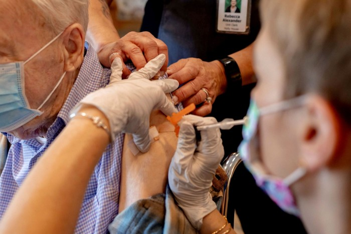 A healthcare worker administers a third dose of the Pfizer-BioNTech Covid-19 vaccine at a care home in Pennsylvania