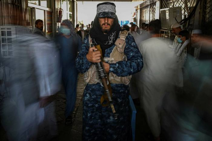 A Taliban fighter stands guard in a Kabul marke