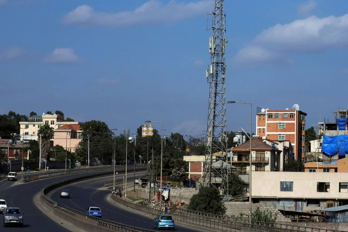 Motorists drive past an Ethio-Telecom network tower in Addis Ababa