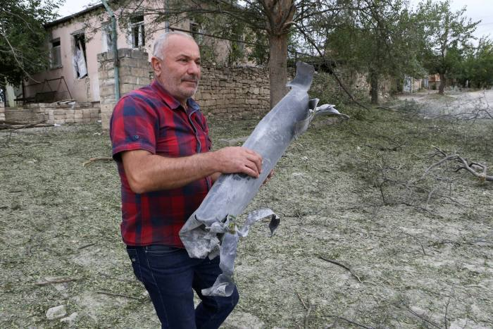 A man carries an ammunition part following what locals said was recent shelling by Azeri forces, in the town of Martuni in the breakaway Nagorno-Karabakh region on Monday