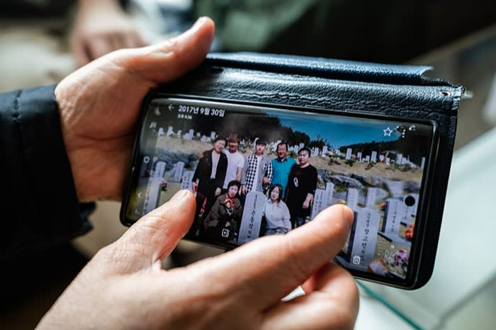 Son Myung-hwa shows a picture of her father's final burial after his remains were returned to his family in South Korea