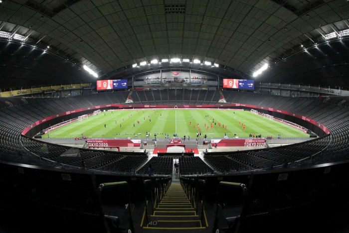 Spectatorless sport: the Japanese and Canadian women's football teams warm up for an Olympic match in Sapporo