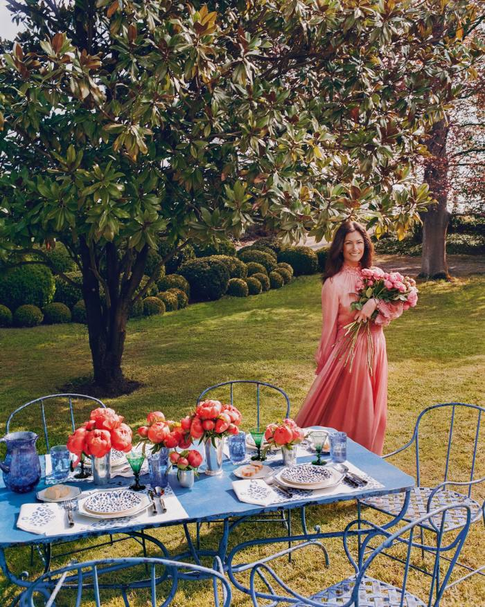 De Castellane in the garden. On the table are Dior Maison Blue Mizza water glasses, £160 each, carafe, £370, dinner plates, £130 each, dessert plates, £100 each, bread plates, £75 each, and placemat and napkin set, £430. Riviera Savana knives, forks and spoons, all £110 each