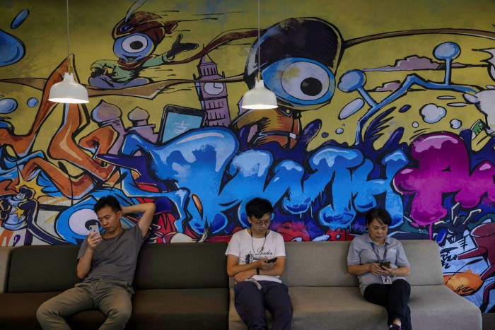 People sit by a mural in an office within the Ant Group headquarters in Hangzhou