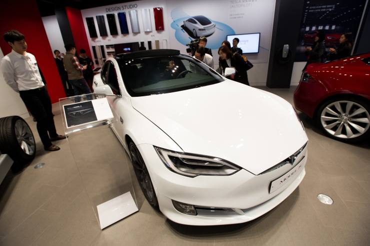 Members of the media look at a Tesla Inc. Model S 90D electric vehicle at the company's showroom in Hanam, Gyeonggi Province, South Korea, on Wednesday, March 15, 2017. Tesla produced almost 84,000 vehicles in 2016 and plans to make half a million in 2018, then 1 million in 2020. Photographer: SeongJoon Cho/Bloomberg