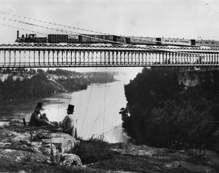 1859:  Two men sit on the cliffs as a steam train crosses the Railway Suspension Bridge over the Niagara River, built in 1855 by John A Roebling to carry the Grand Trunk Railway between Canada and New York State, USA. (Looking south towards Niagara Falls from the American bank).  (Photo by William England/London Stereoscopic Company/Getty Images)