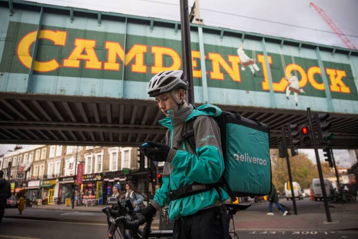 Restaurant Food Delivery company 'Deliveroo' employee, Billy Shannon looks for an address while working in Camden Town, north London in November 17, 2016.  							Lunch hour has just started in the north London borough of Camden, which means it's crunch time for Billy Shannon, a fresh-faced food-delivery courier. Dressed in thermal clothing to ward off the autumnal cold, the 18-year-old jumps on his bike as an order comes in, mindful that he is paid not by the hour, but by the number of deliveries he makes. 							 / AFP / DANIEL LEAL-OLIVAS / TO GO WITH AFP STORY BY ALICE TIDEY        (Photo credit should read DANIEL LEAL-OLIVAS/AFP/Getty Images)