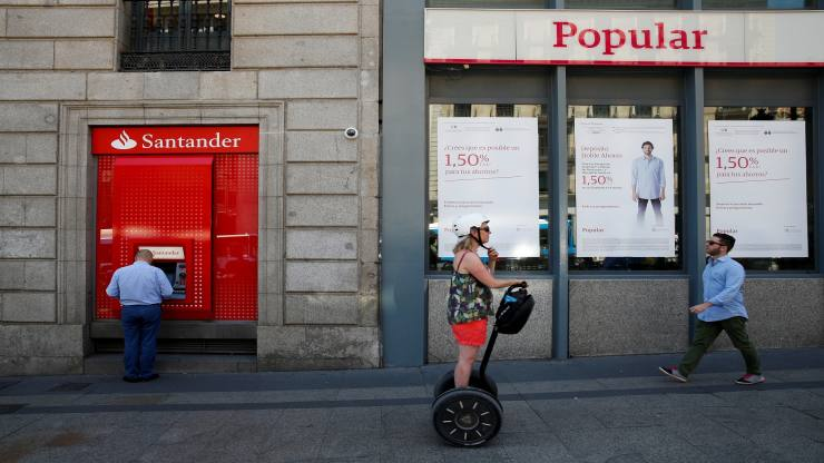 A man uses a cash dispenser at a branch of Spain's biggest bank Santander next to a Banco Popular branch on the same day Santander announced that it would buy struggling rival Banco Popular for a nominal one euro after European authorities determined the lender was on the verge of insolvency, in Madrid, Spain June 7, 2017. REUTERS/Juan Medina TPX IMAGES OF THE DAY