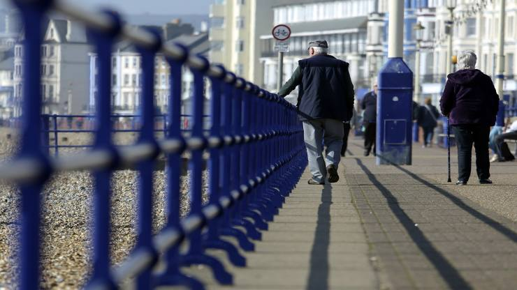 Pedestrians walk along the beachfront promenade in Eastbourne, U.K., on Tuesday, April 1, 2014. Pensioners and savers have seen returns on their money shrink since the financial crisis drove interest rates to a record low. Photographer: Chris Ratcliffe/Bloomberg