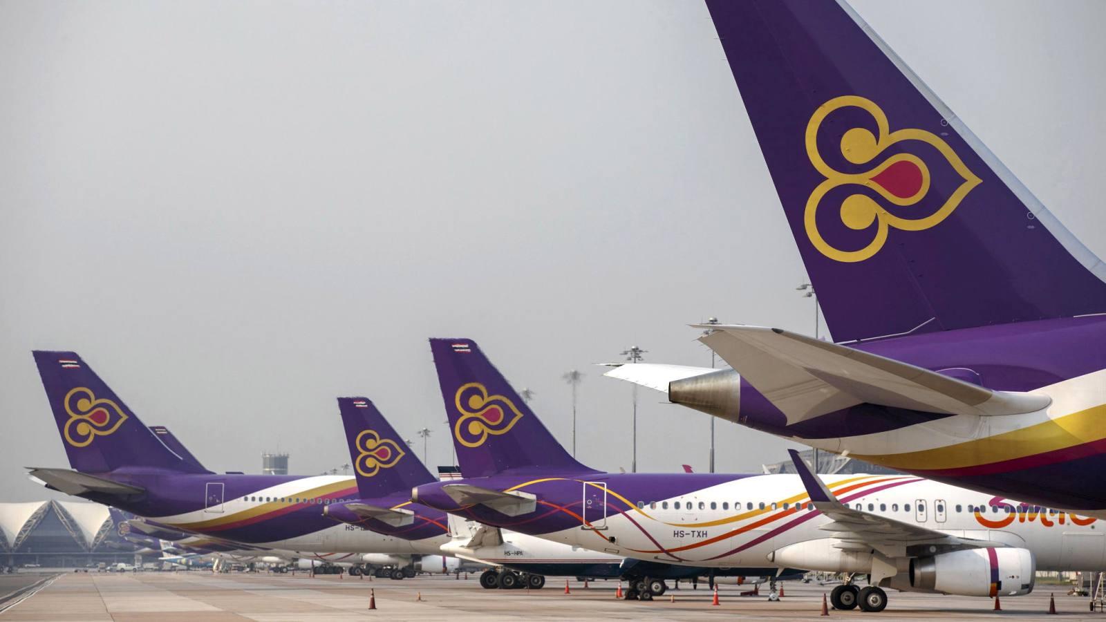 Thai Airways aircraft are parked on the tarmac at Bangkok's Suvarnabhumi International Airport.