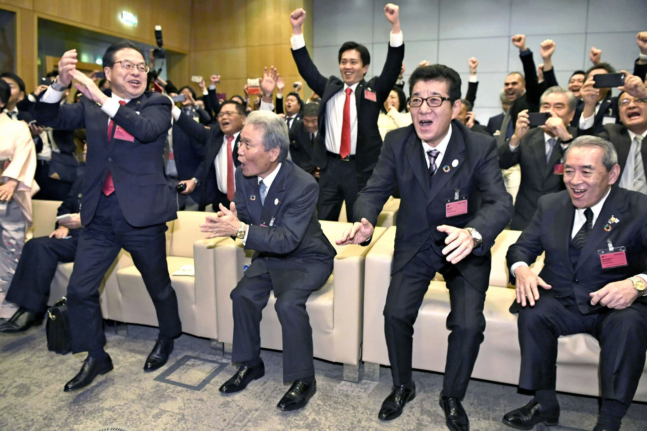 Keidanren honorary chair Sadayuki Sakakibara, second from left, celebrates with other Japanese government officials and business leaders after the host city for the World Expo in 2025 was announced.