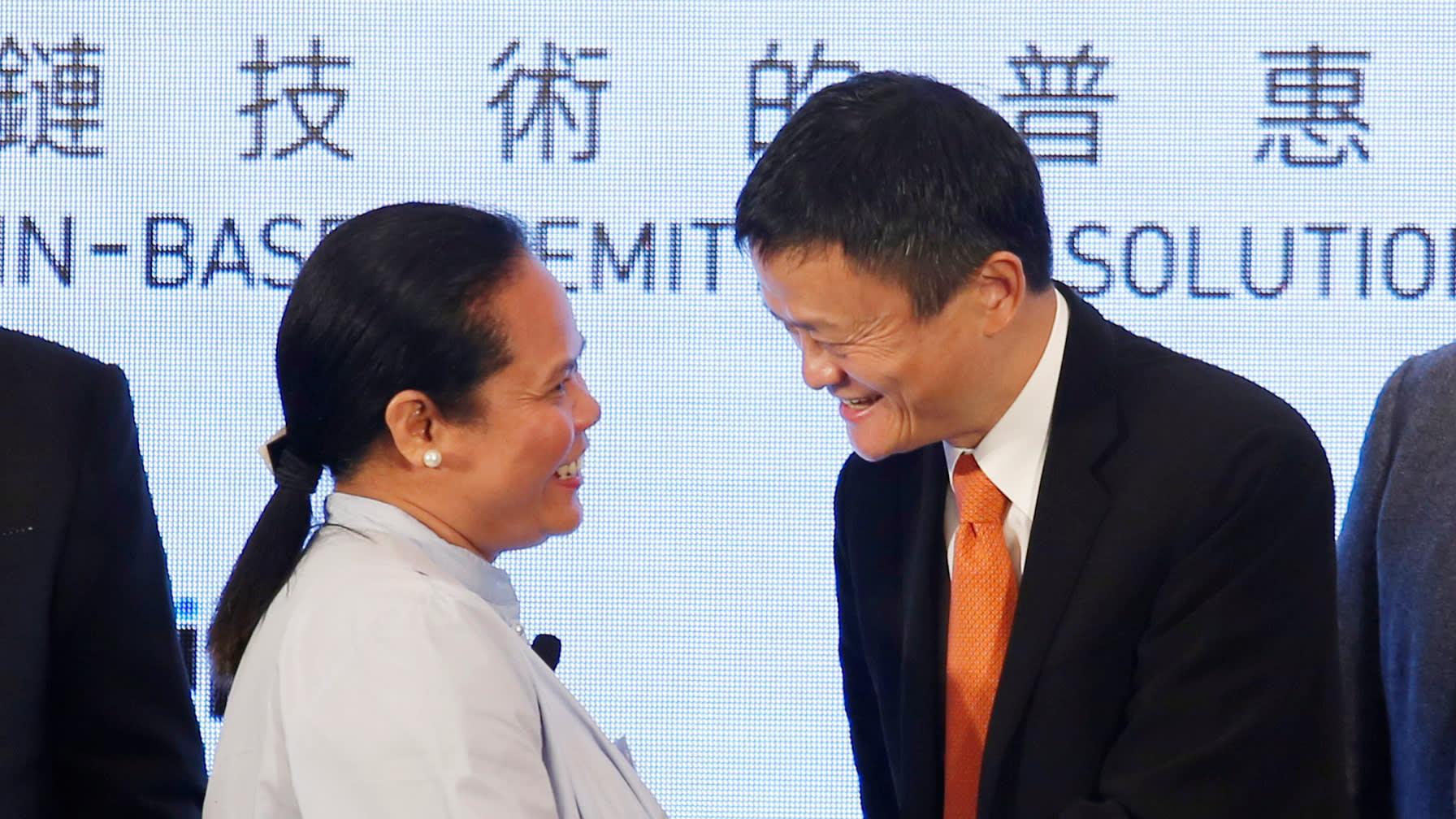 Alibaba Group's Jack Ma, right, greets aFilipino guestat a news conference Monday