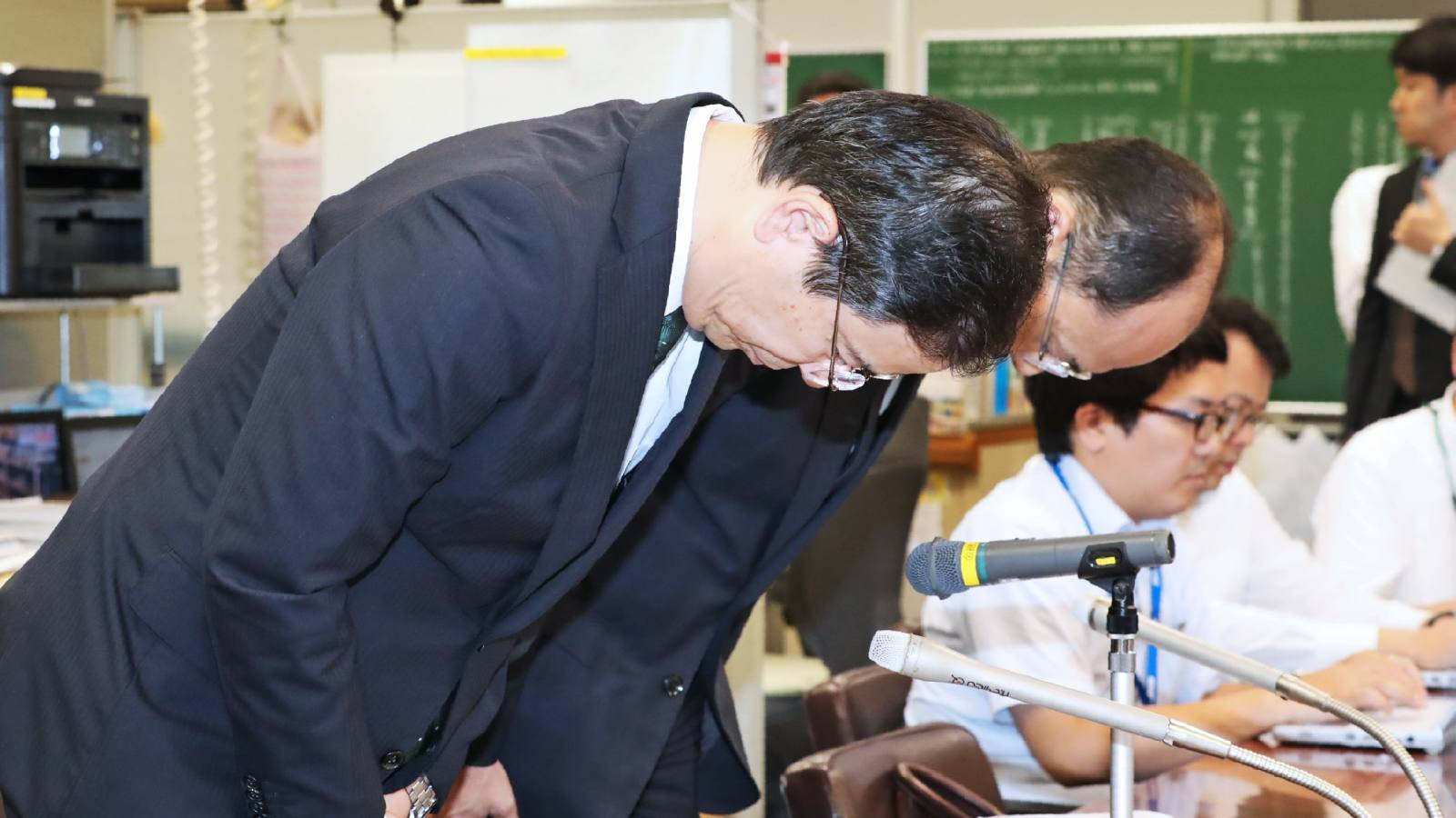 Higashi-Nippon Bank director Takashi Sakai, front, bowed in apology at a press conference Friday about the lender's loan misbehavior.