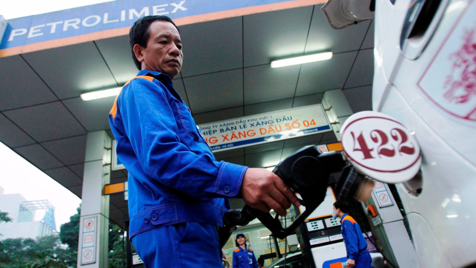 A man pumps gasoline at a gas station in Hanoi, run by Vietnam's top fuel importer and distributor Petrolimex.