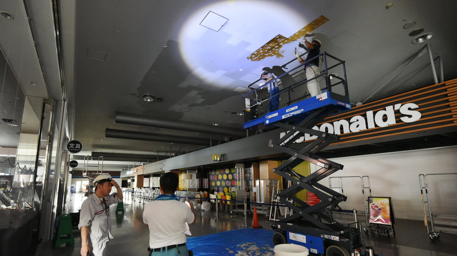Workers fix a ceiling in Terminal 1 of Kansai International Airport, damaged heavily by Typhoon Jebi. (Photo by Tomoki Mera)