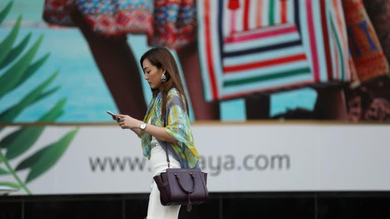 woman walks past luxury fashion ad
