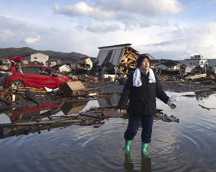 A woman walks through the rubble of her home, destroyed by the tsunami which followed the 2011 earthquake