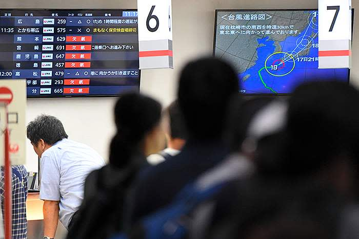Airport passengers, stranded by a typhoon, in front of a Weathernews screen