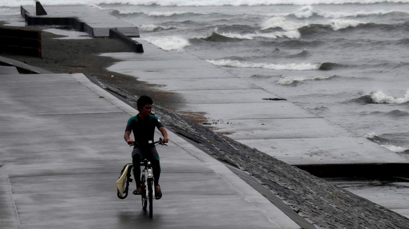 A man leaves after surfing near Tokyo as Typhoon 18 bears down