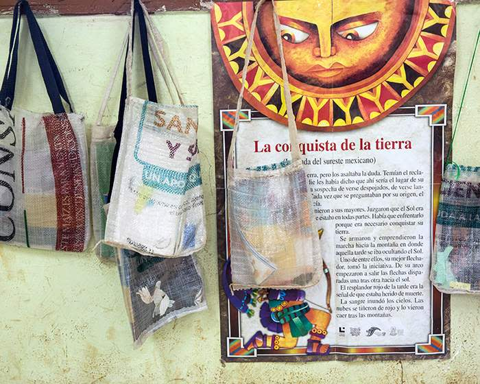 Book bags made of recycled sacks hang in front of a poster about the ancient Maya