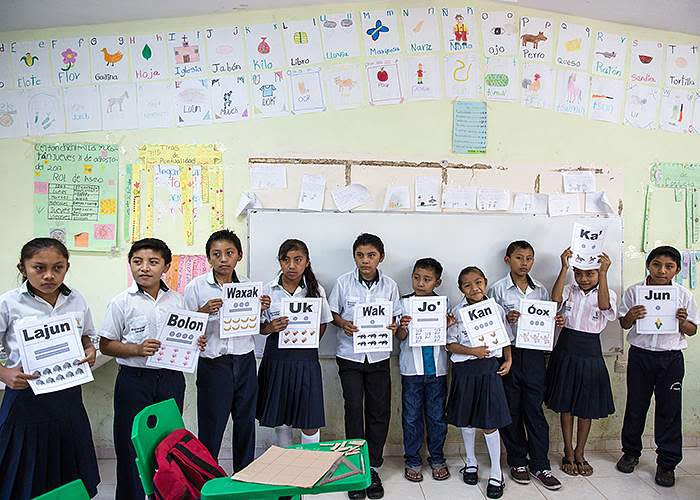 Students hold signs showing the Maya names for the numbers one to 10