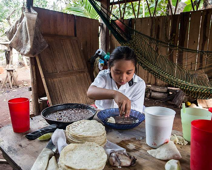 Yuri eats a lunch of tortilla and beans at home in the remote village of Celtún