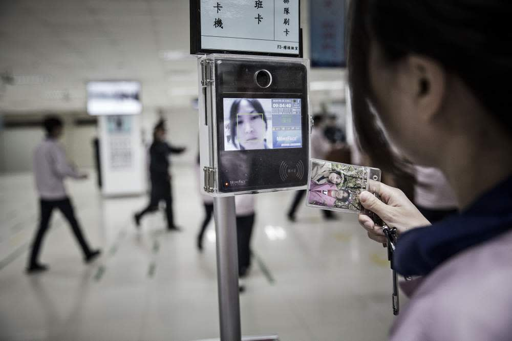 An employee uses a facial recognition device at a factory in Shanghai