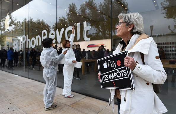 "A woman holds a sign reading ""Apple pay your taxes"" during a protest against tax evasion in France"