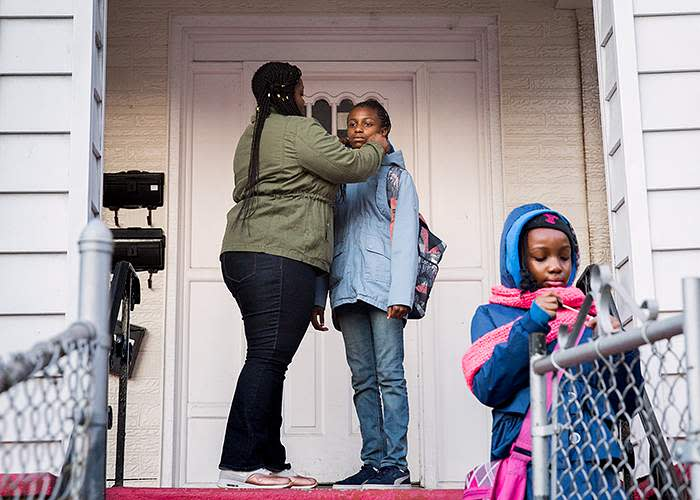 Armani (centre), with her mother, Arlene, and sister, Jameeyah, outside their home in Brooklyn