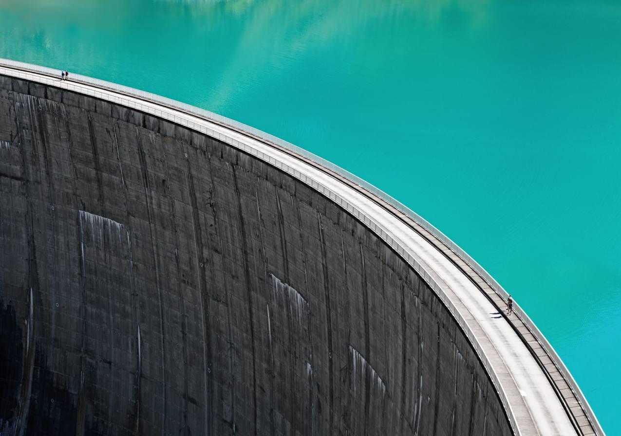 People walking on edge of Stausee Mooserboden Dam, Kaprun, Austria