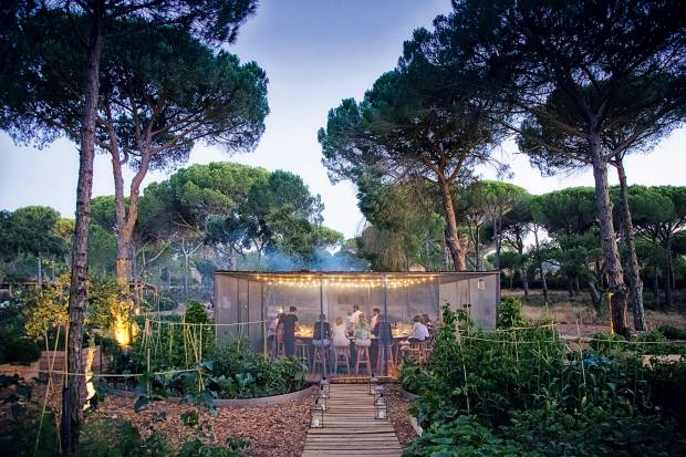 Guests dine in the grounds of the Sublime hotel in Comporta, whose restaurant is built to resemble a traditional rice storage warehouse