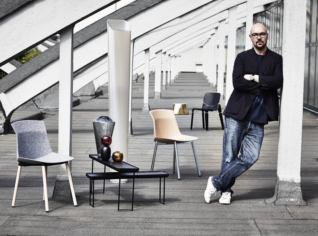 Luca Nichetto at his studio in Venice with a selection of his designs. From far left: Cassina wood and metal Torei tables, from £882. Salviati glass Millebolle vase (on table), from €555. Gallery Pascale glass and ceramic Les Poupées combined candle holders and vases (on table), from SKr995 (about £96). Foscarini Empire floor lamp, £830. Cassina leather and aluminium Motek chair, £852. Moroso Fool on the Hill stool (no longer in production). Offecct wood and textile Robo chair, €640