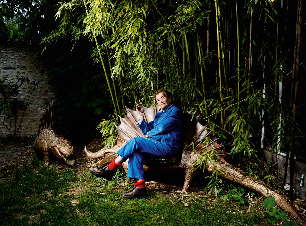 Claude Lalanne in the garden of her home near Fontainebleau, with two of her 2012 bronze La Femme du Crocodile sculptures