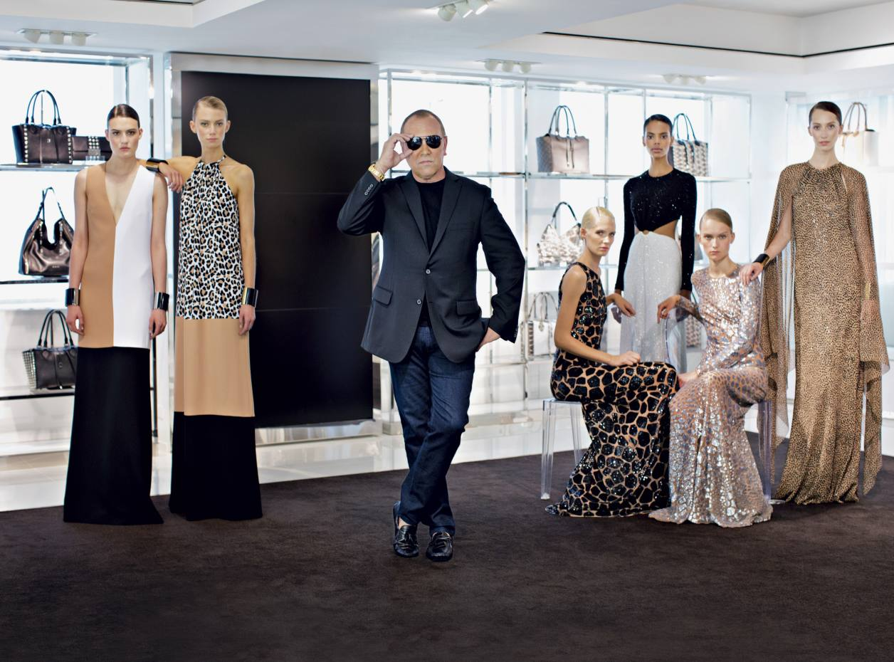 Michael Kors with looks from his 2013 resort collection. Dresses from far left: column dress in crepe sable, £1,792. Leopard-print crepe column dress, £1,699. Giraffe-print one-shoulder gown in sequined tulle, £9,727. Jersey and crystal cutout gown, price on request. Giraffe-print gown in sequined chiffon, £10,214. Ocelot-print bias-cut gown in sequined tulle, price on request