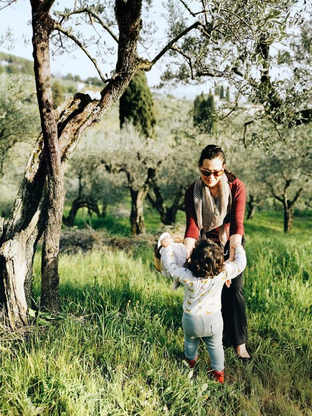 Emiko and her daughter Luna among olive trees near their home