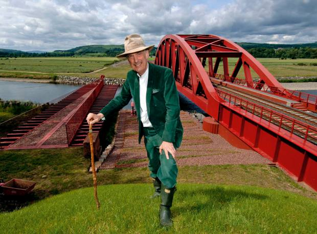 Charles Jencks in the Portrack House gardens, Dumfries & Galloway, with the bridge for mainline trains on the London-Glasgow line in the background