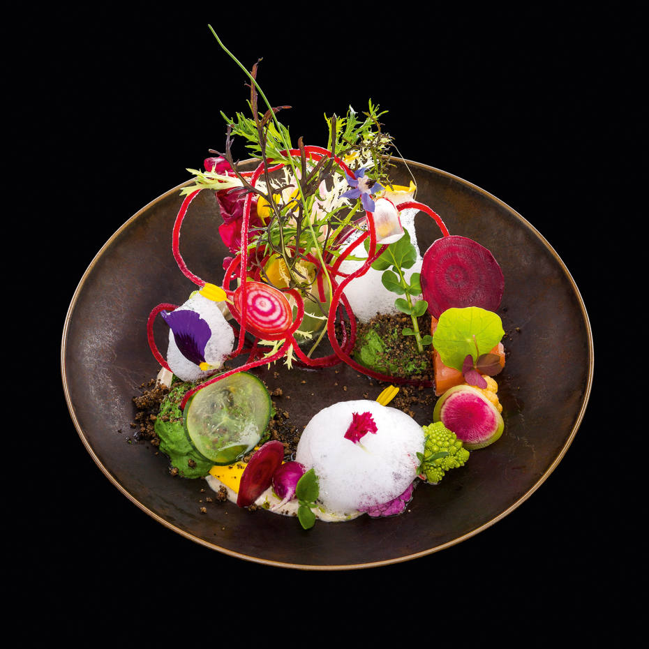 An elegant jumble of herbs and barely cooked vegetables concealing a tranche of smoked salmon, with a lemon emulsion, tomato vinaigrette and dusting of dried black olives, all collapsing into a light, chilled rocket soup
