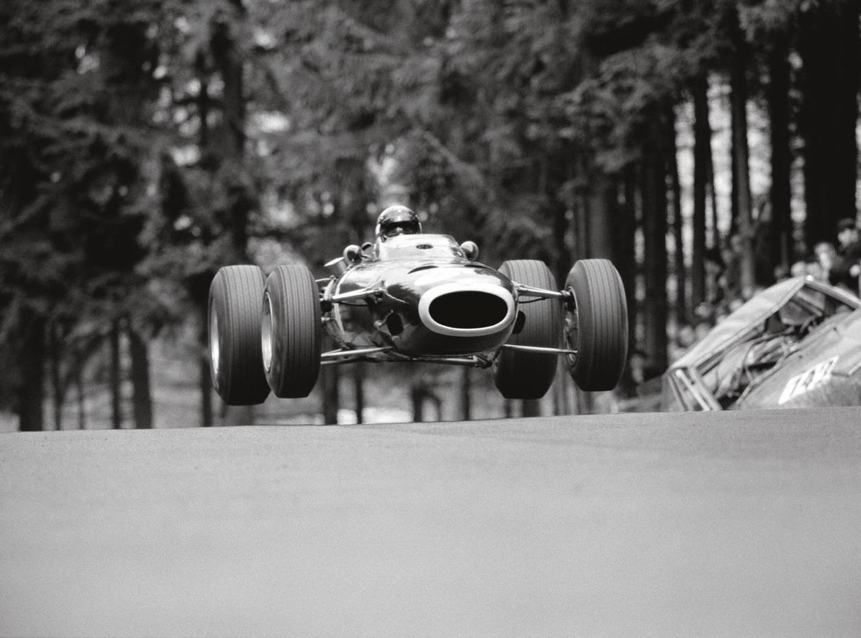 Jackie Stewart drives his BRM 261 past a crashed touring car in the 1966 German Grand Prix