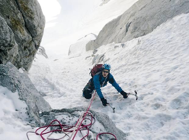 Tarquin climbs with ice axes.