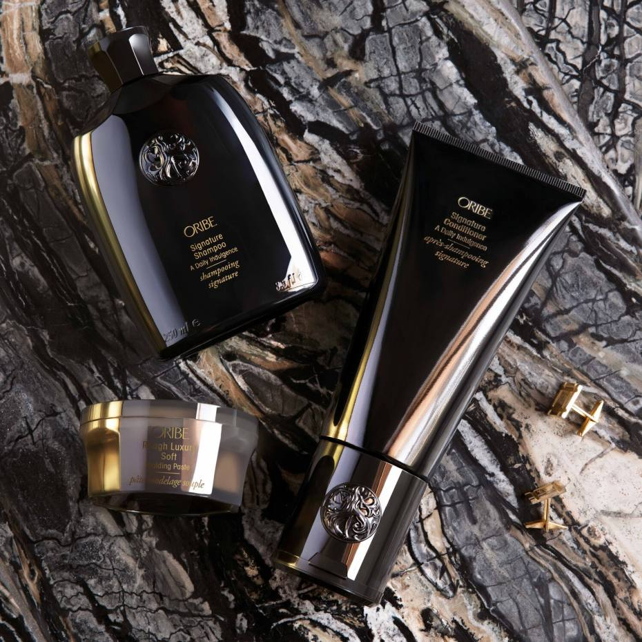 Oribe Rough Luxury Soft Moulding Paste (bottom left), alongside the brand's signature shampoo and conditioner