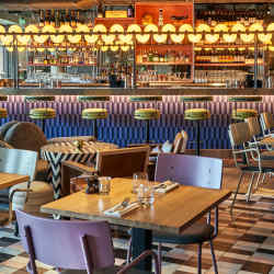 The buzzy atmosphere of Bluebird Café is reflected in its bright furniture, bold geometric designs and illuminated bar