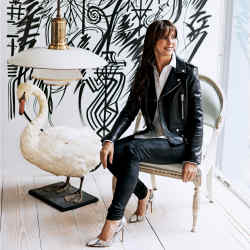 Jill Dienst on an antique Gustavian chair, $12,500, near a Poul Henningsen copper and frosted-glass pendant light, $28,500