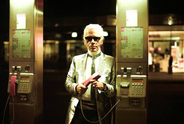 Biskup followed the designer around Berlin for an evening in 2002; here Lagerfeld uses a payphone