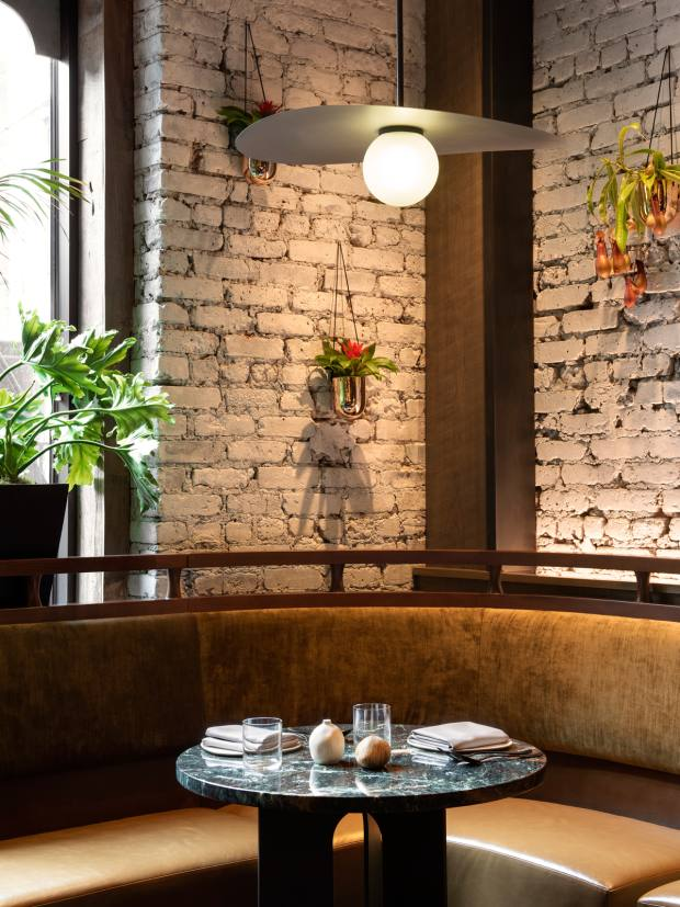 The restaurant has a relaxed vibe with leather banquettes and teak details against whitewashed brick walls