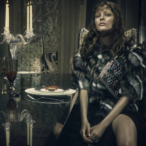 Fendi mink, fox- and raccoon‑fur coat, £10,000, chiffon pleated skirt, £1,430, and embellished tortoise and ayers-skin Baguette bag, £2,390Fendi Casa Macassar-ebony Galileo dining table, from £26,920; solid-beech, leather and silk-mix Cerva chairs, from £3,030; handmade Murano-glass candlesticks, from £2,090; handmade Murano glasses, from £300; handmade Murano-glass Ottavia fruit stand, from £2,100; and bone-china Art de la Table plate from the Heritage collection, from £190