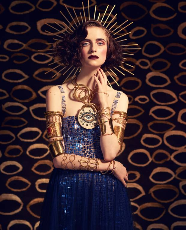 Dior mirror mosaic tulle playsuit, £5,600, and tulle skirt, £3,600. Headdress, stylist's own. Pebble London gold metal flexible bangles (worn as necklace), £30 each. Eye pendant, stylist's own. From top of right arm: Pebble London gold metal flexible bangle, £30, brass multi-circles bangle, £70, gold plate, agate, pearl and semiprecious stone cuff, £165, gold plate and semiprecious faceted cabochon bangles, £45 each, brass cuff, £55, gold plated bangle, £90, brass bangle, £45, brass bangle, £70, and gold plate and semiprecious cabochon cuff, £195. From top of left arm: Pebble London gold metal flexible bangle, £30, gold metal curled band armlet, £75, gold metal wire cuff, £55, gold metal flexible bangle, £30, gold plate and semiprecious faceted cabochon bangles, £45 each, gold plate and semiprecious crystal cabochon cuff, £165, and gold metal crinkle cuff, £55. Background: Allegra Hicks for The Rug Company handknotted Tibetan wool/silk Pebbles Brown rug, from £3,014